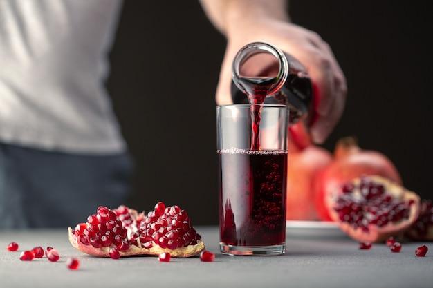 Männliche hand, die granatapfelsaft von einer flasche in ein glas gießt