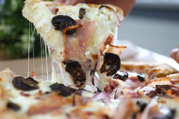 Männliche hand, die großes stück der leckeren frischen pizza hält