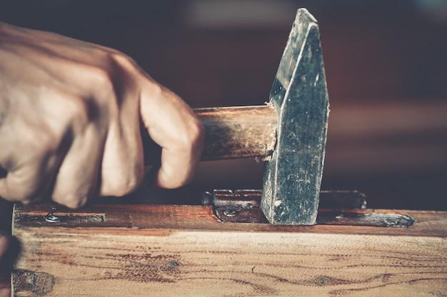 Männliche hand, die hammer hält