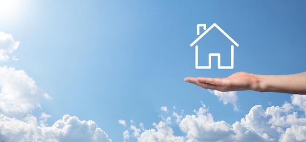 Männliche hand, die hausikone auf blauem hintergrund hält. sachversicherung und sicherheitskonzept. immobilienkonzept. banner mit kopienraum.