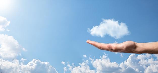Männliche hand, die hausikone auf blauem hintergrund hält. sachversicherungs- und sicherheitskonzept. immobilienkonzept. wetterbedingungen, bewölkung. banner mit kopienraum.