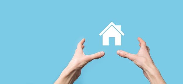 Männliche hand, die hausikone auf blauem hintergrund hält. sachversicherungs- und sicherheitskonzept. immobilienkonzept.