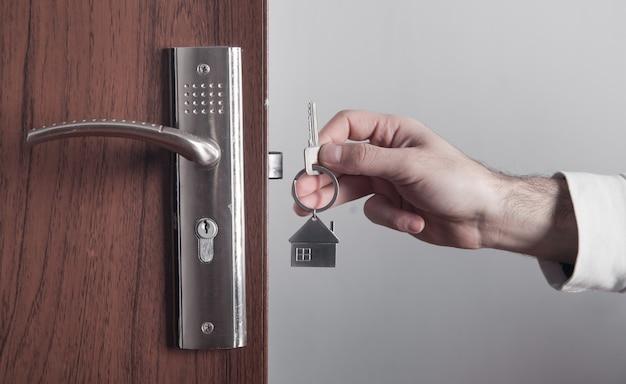 Männliche hand, die hausschlüssel zu hause hält.