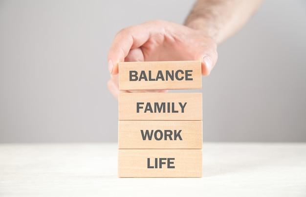 Männliche hand, die holzblock zeigt. leben. arbeit. familie. balance