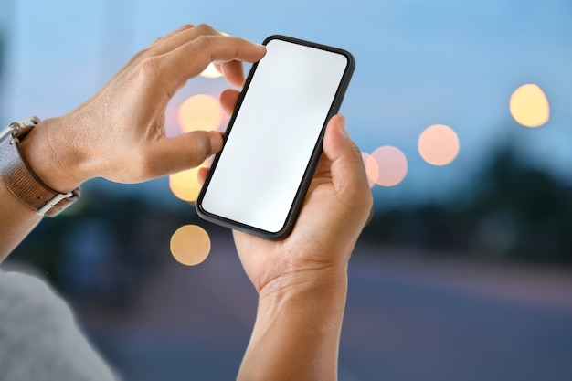 Männliche hand, die intelligentes mobiltelefon des leeren bildschirms nachts straße hält.