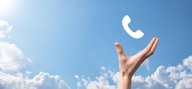 Männliche hand, die intelligentes mobiltelefon mit telefonsymbol hält. rufen sie jetzt geschäftskommunikations-unterstützungszentrum-kundendienst-technologiekonzept an.