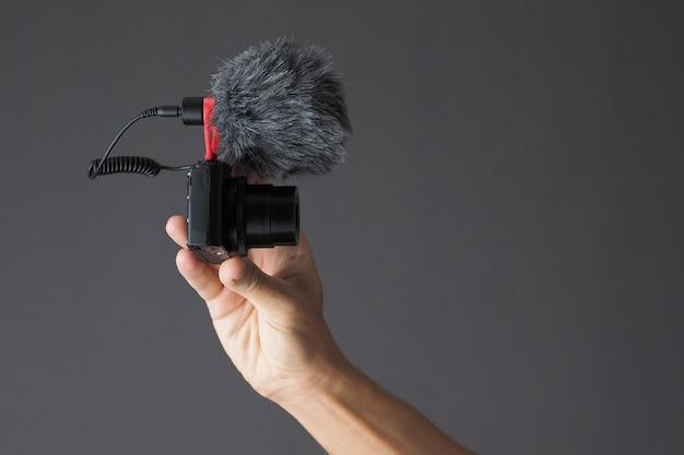 Männliche hand, die kompaktkamera mit mikrofon hält