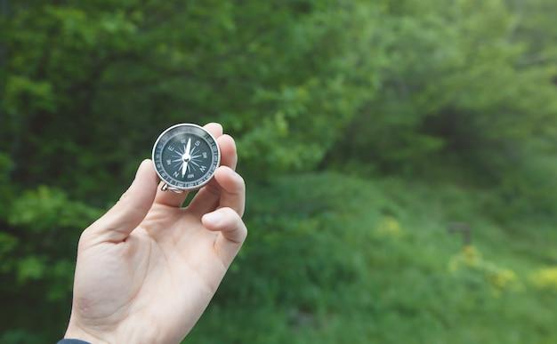 Männliche hand, die kompass im wald zeigt.
