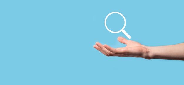 Männliche hand, die lupe hält, suchsymbol auf blauem hintergrund. konzept suchmaschinenoptimierung, kundenunterstützung. durchsuchen von internetdateninformationen. netzwerkkonzept.