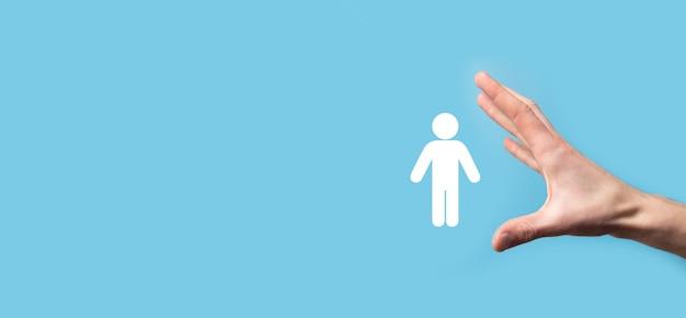 Männliche hand, die menschliches symbol auf blauem hintergrund hält. personal hr management recruitment employment headhunting concept. wählen sie das konzept des teamleiters. männliche hand klicken auf mannsymbol. banner, spase kopieren.