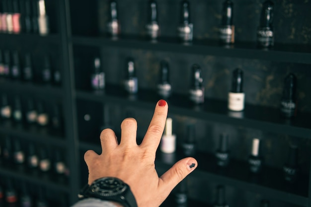 Männliche hand, die nagellack aus der mehrfarbigen palette im schönheitssalon auswählt. einkaufen in einem schönheitssalon