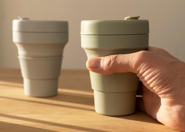 Männliche hand, die öko-kaffeetasse vom holztisch mit schönem tageslicht vom fenster hält oder nimmt.