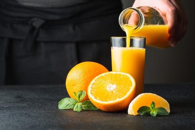 Männliche hand, die orangensaft aus einer flasche in ein glas gießt. in der nähe der ganzen, halben und einer orangenscheibe.