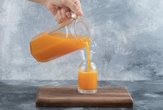 Männliche hand, die orangensaft in glas gießt.
