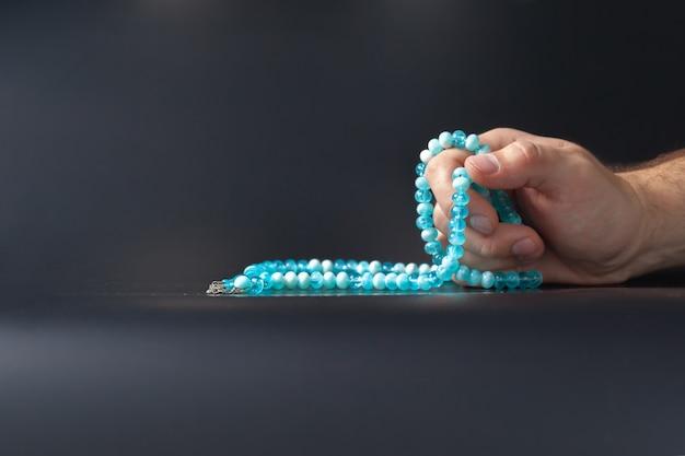 Männliche hand, die perlen hält