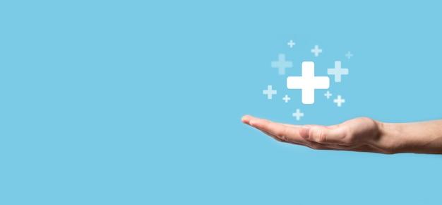 Männliche hand, die plus symbol auf blauer oberfläche hält