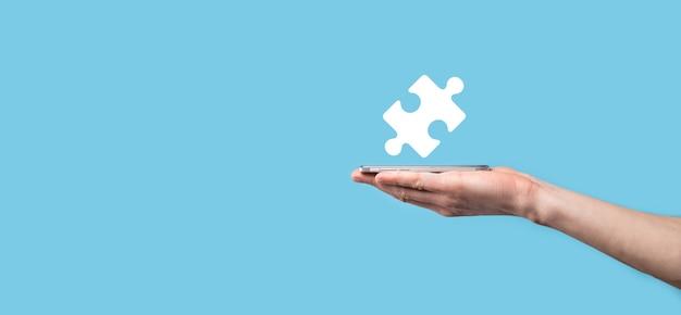 Männliche hand, die puzzlesymbol auf blauem hintergrund hält. stücke, die die fusion von zwei unternehmen oder joint venture, partnerschaft, fusionen und akquisitionskonzept darstellen.