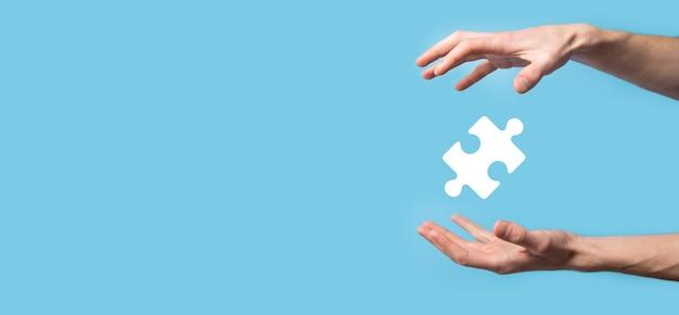 Männliche hand, die puzzlesymbol auf blauem hintergrund hält.
