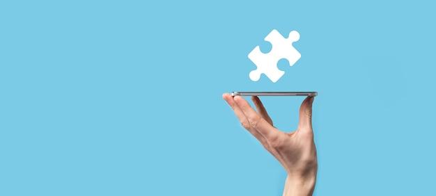 Männliche hand, die puzzlesymbol auf blauer oberfläche hält