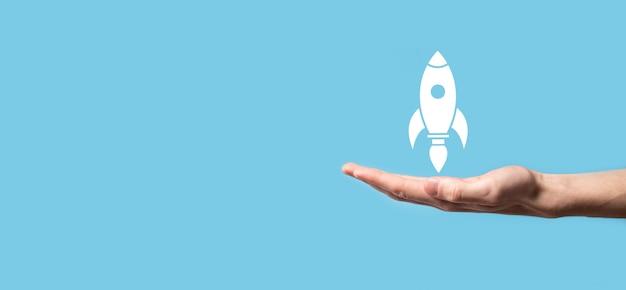 Männliche hand, die raketensymbol hält, das abhebt, start auf blauer oberfläche