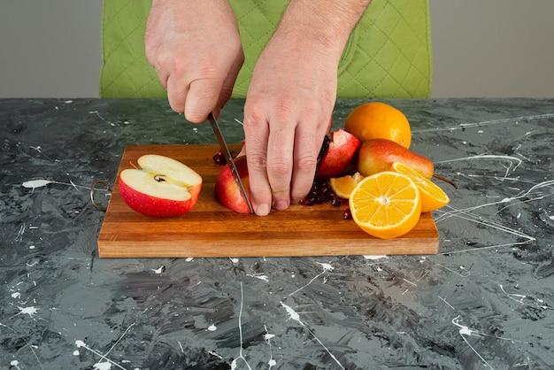 Männliche hand, die roten apfel auf holzbrett auf tisch schneidet.