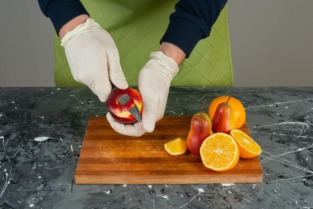 Männliche hand, die roten apfel oben auf holzbrett auf tisch schält.