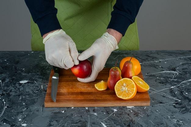 Männliche hand, die roten apfel oben auf holzbrett auf tisch schneidet.