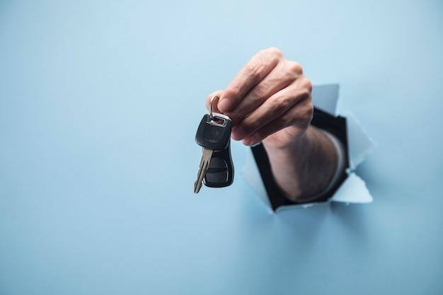 Männliche hand, die schlüssel auf blauer szene hält
