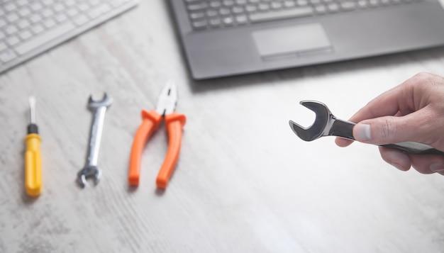 Männliche hand, die schraubenschlüssel zeigt. computertastaturen auf dem schreibtisch. it-service. unterstützung