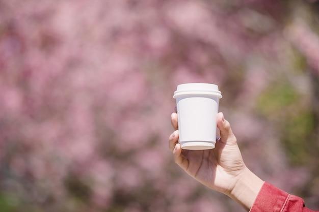 Männliche hand, die sich von einer weißen schale heißem kaffee vor rosa kirschblüte zeigt