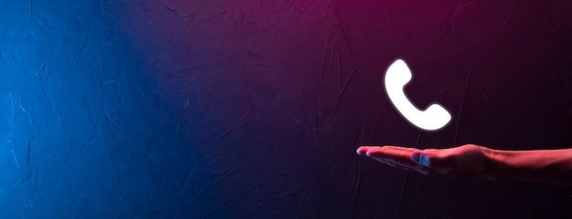 Männliche hand, die smartphone mit telefonsymbol hält. rufen sie jetzt business communication support center customer service technology concept an. neonrot, blauer lichthintergrund