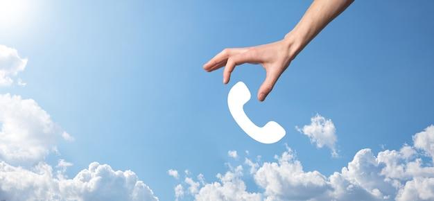 Männliche hand, die smartphone mit telefonsymbol hält. rufen sie jetzt business communication support center customer service technology concept an.