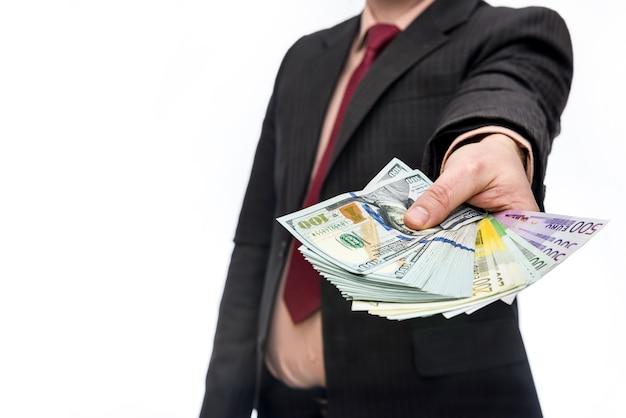 Männliche hand, die stapel von dollar- und euro-banknoten anbietet