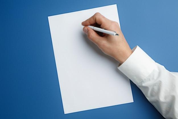 Männliche hand, die stift hält und auf leeres blatt auf blau schreibt