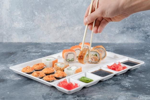 Männliche hand, die sushi-rolle mit stäbchen vom weißen teller nimmt