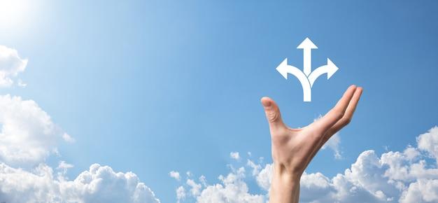 Männliche hand, die symbol mit drei richtungen-symbol auf blauem hintergrund hält. zweifel, zwischen drei verschiedenen möglichkeiten wählen zu müssen, die durch pfeile angezeigt werden, die in die entgegengesetzte richtung weisen. wege