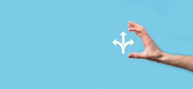 Männliche hand, die symbol mit symbol für drei richtungen auf blauem hintergrund hält, zweifelt daran, zwischen drei verschiedenen auswahlmöglichkeiten wählen zu müssen, die durch pfeile angezeigt werden, die in drei richtungen in das konzept der entgegengesetzten richtung zeigen