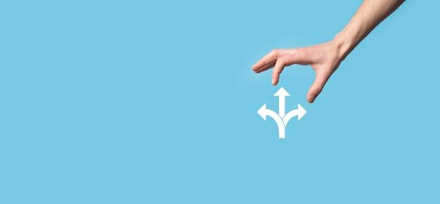 Männliche hand, die symbol mit symbol für drei richtungen hält