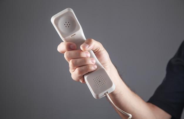 Männliche hand, die telefonhörer hält.