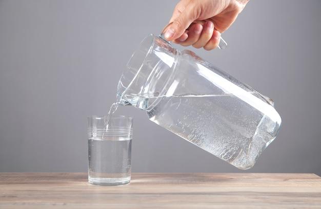 Männliche hand, die wasser in glas gießt. gesundes getränk