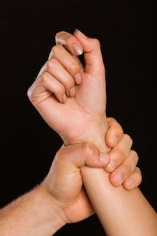 Männliche hand, die weibliches handgelenk ergreift