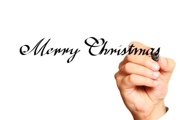 Männliche hand, die weihnachtswünsche über weißem hintergrund schreibt
