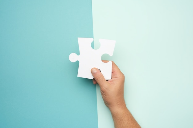 Männliche hand, die weiße leere puzzles des großen papiers, geschäftskonzept hält