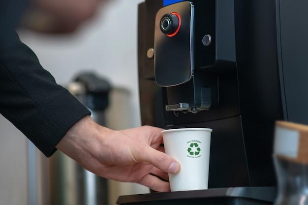 Männliche hand, die weißen pappbecher mit grünem zeichen nahe stand auf getränkemaschine hält