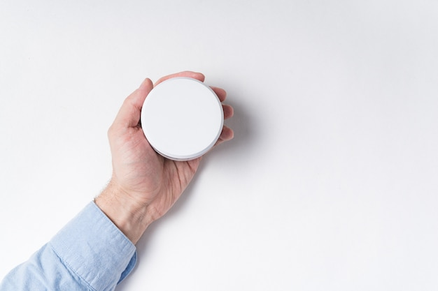 Männliche hand, die weißes kosmetisches glas hält. modell auf weißem hintergrund.