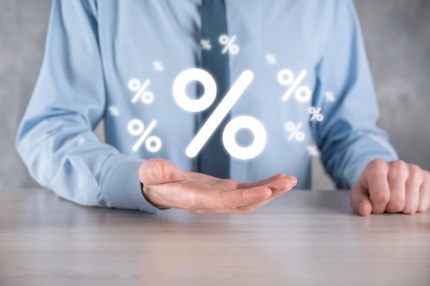 Männliche hand, die zinssatzprozentsymbol auf blauem hintergrund hält. zinskonzept für finanz- und hypothekenzinsen. banner mit kopierraum
