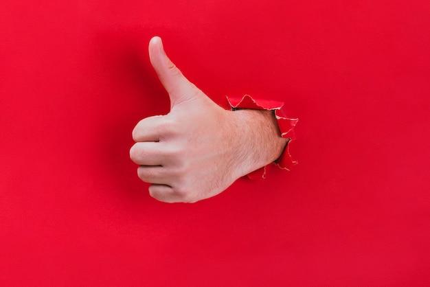 Männliche hand durchbricht das rote papier und zeigt seinen daumen.