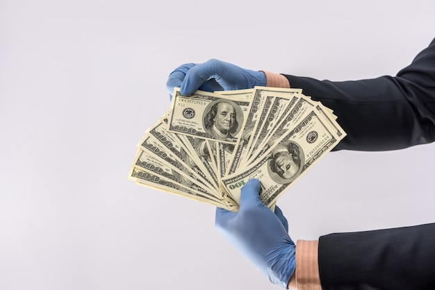 Männliche hand geben dollar, um in schutzhandschuhen aus sicherheitsgründen isoliert auf weißem hintergrund zu zahlen. medizinisches konzept covid 19 coronavirus