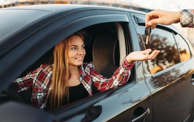 Männliche hand gibt die autoschlüssel an weibliche fahrerin