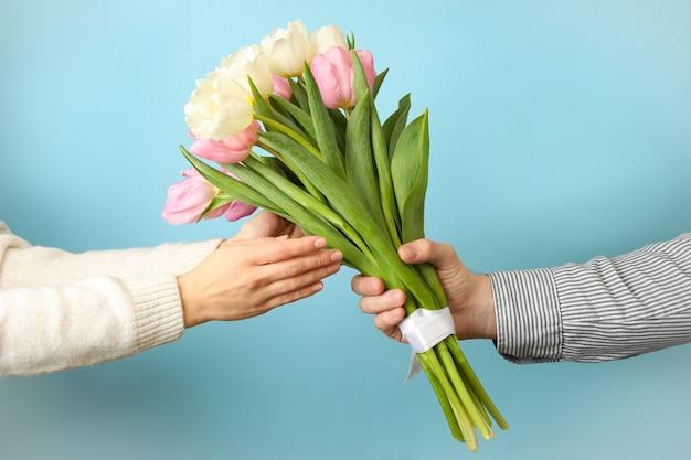 Männliche hand gibt tulpenstrauß zur weiblichen hand auf blauem hintergrund